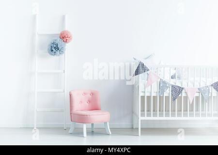 Chaise rose à côté du blanc berceau dans la chambre de bébé pastel avec échelle de l'intérieur. Photo réelle