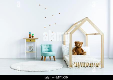 Ours sur lit en bois à côté du fauteuil bleu blanc dans la chambre de l'enfant intérieur. Photo réelle