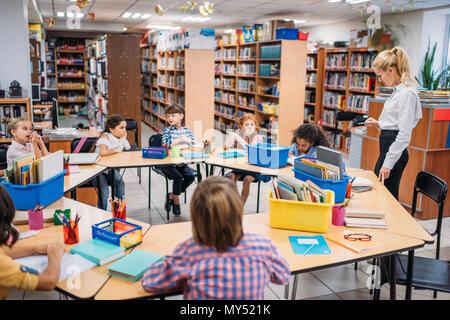 Beau jeune enseignant leçon donner aux enfants dans la bibliothèque Banque D'Images