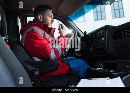 Jeune beau mâle paramedic parler par radio portable Banque D'Images