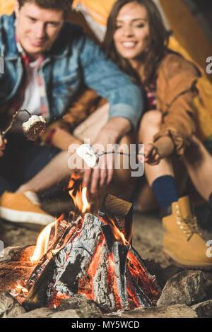 Jeune couple guimauve torréfaction sur des bâtons en voyage de camping Banque D'Images