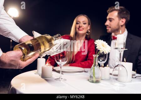 Waiter pouring wine alors que couple having date romantique au restaurant le Jour de Valentines Banque D'Images