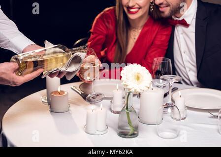 Portrait of waiter pouring wine alors que couple having date romantique au restaurant Banque D'Images
