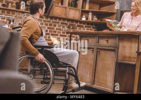 Portrait de femme avec homme handicapé en fauteuil roulant: cuire le dîner ensemble à la maison Banque D'Images