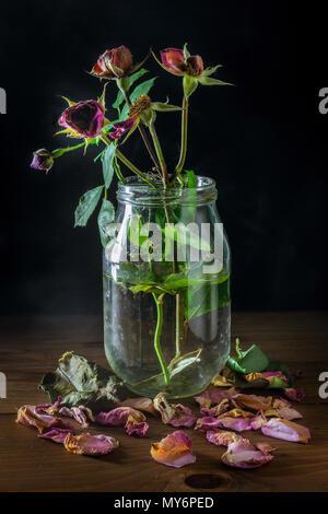 Nature morte avec roses fanées dans le vase en verre sur la table en bois Banque D'Images