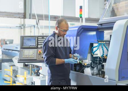 Engineer inspecting partie pour tour automatique à l'usine d'ingénierie