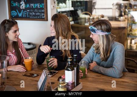 Trois jeunes amis féminins avec du jus de légumes chatting in cafe Banque D'Images