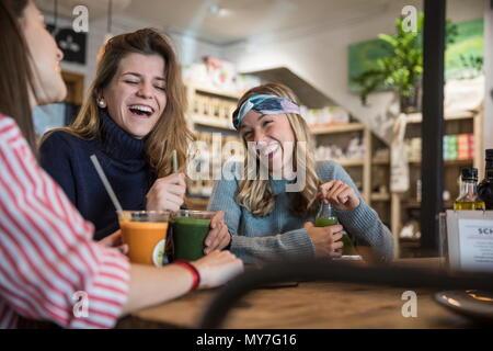 Les trois amis, assis dans un café, boire des smoothies, laughing Banque D'Images