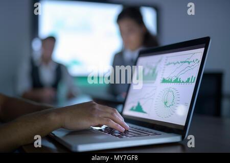 Businessman affichage des tableaux et des graphiques sur ordinateur portable en réunion d'affaires, Close up Banque D'Images