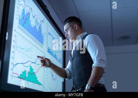 Businessman affichage des tableaux et des graphiques sur l'écran interactif en réunion d'affaires Banque D'Images