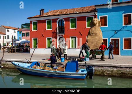 Les femmes achètent des fruits et légumes frais d'un magasin mobile comme un groupe d'hommes poussent un carnaval flotter le long de la rue, l'île de Burano, Venise, Italie