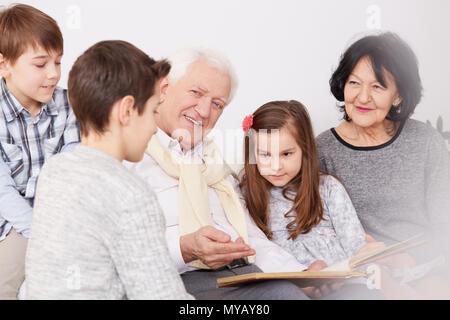 Famille heureuse en regardant une vieille photo album Banque D'Images