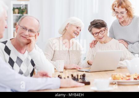 Deux hommes plus âgés jouant aux échecs et trois hauts women using laptop