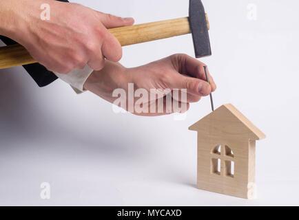 Marteaux homme un clou avec un marteau dans une maison en bois miniature sur un fond blanc. Concept de la réparation des maisons. Le travailleur effectue des travaux de réparation dans th