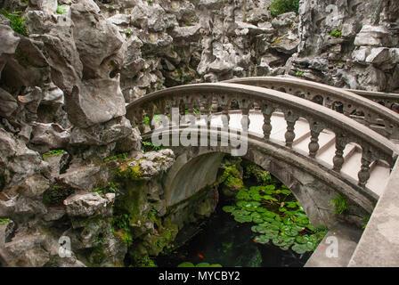 Pont en arc de pierre ancienne sur l'étang à l'intérieur jardin chinois Banque D'Images
