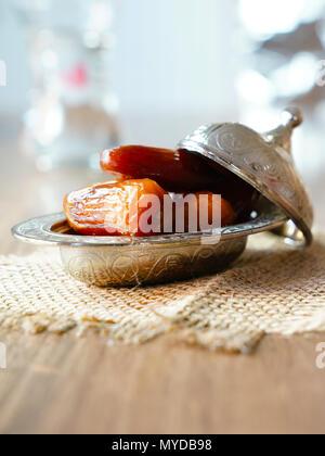 Dates de fruits frais dans un bol en métal argenté sur un morceau de sacs sur table en bois de noyer Banque D'Images