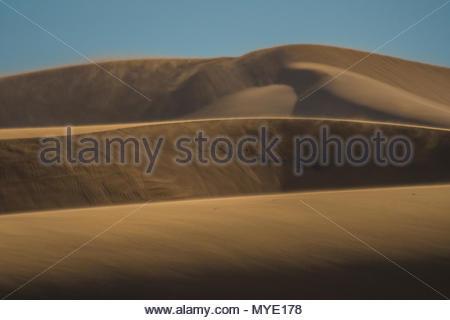 Strong winds blow off de sable du désert de grandes dunes de sable. Banque D'Images