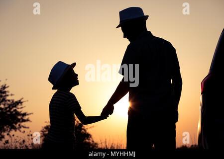 Père et fils jouer dans le parc à l'heure de coucher du soleil. Les gens s'amusant sur le terrain. Concept de famille accueillante et des vacances d'été. Banque D'Images