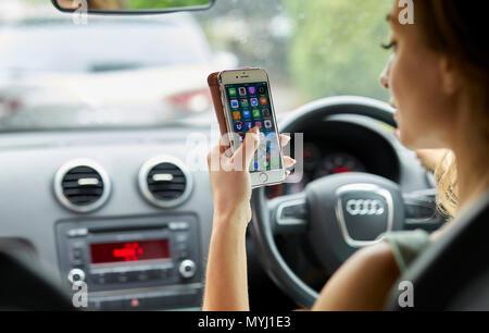 Femme au volant pendant l'utilisation de téléphone mobile Banque D'Images