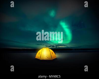 Dans le désert les lumières du Nord (aurores boréales) danse à travers le ciel de nuit en Suède, au-dessus de l'éclairage incandescent de la tente de camping. Pho Banque D'Images