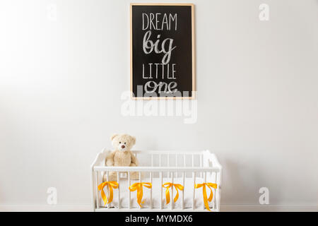 Tiré d'un lit avec un ours et un tableau noir sur un mur dans une pépinière prix Banque D'Images