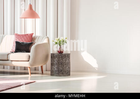 Salon simple intérieur avec coussins rose et gris sur canapé beige et roses sur métal Banque D'Images