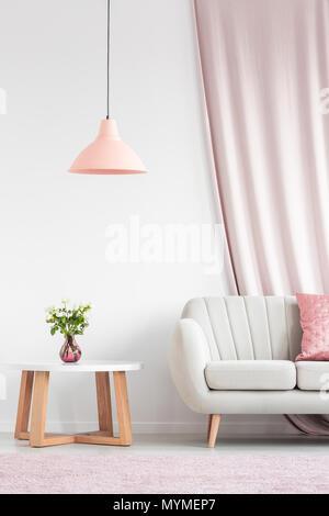 Salon lumineux avec canapé beige intérieur, pêche lampe, table en bois et roses dans vase rose Banque D'Images