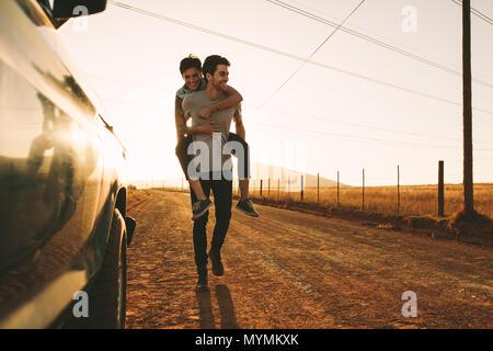 Woman piggy à cheval sur un homme à l'extérieur dans la campagne. Homme portant une femme sur son dos tandis que sur un voyage sur la route. Banque D'Images