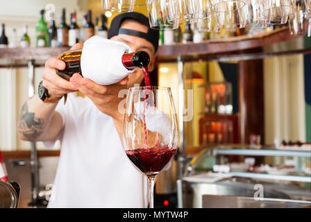 Barman verse un verre de vin rouge au bar Banque D'Images