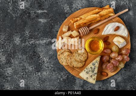 Assortiment de fromage avec du miel, des noix et du raisin sur une planche à découper, vue du dessus.