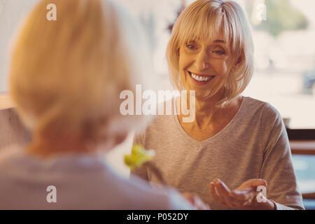 Cheerful woman lui disant de nouvelles d'amis au cours de brunch dans cafe Banque D'Images