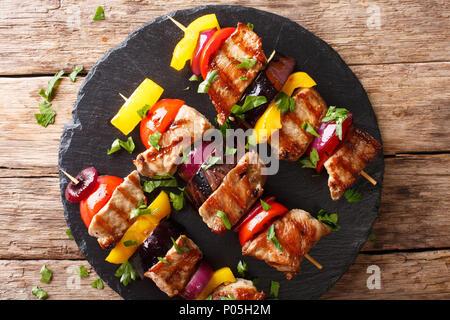 Brochettes de porc grillé juteux avec les tomates, le poivre, les oignons et les aubergines sur une plaque en ardoise sur une table horizontale. haut Vue de dessus Banque D'Images
