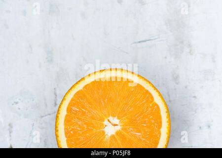 Tranche de juteux mûr Vibrant vif couleur orange sur fond gris métal Pierre Béton. Les aliments à haute résolution de l'affiche. Les vitamines d'été mourir sain Vegan Banque D'Images