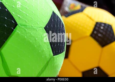 Ballons de football éponge à vendre étendus dehors un magasin en été.