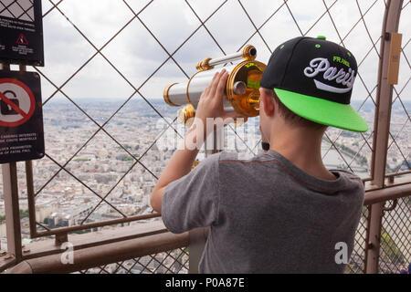 Un garçon de neuf ans à l'aide d'un télescope à monnayeur en haut de la Tour Eiffel, Paris, France, Europe. Banque D'Images