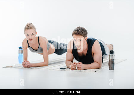 Belle jeune couple plank exercice isolated on white Banque D'Images