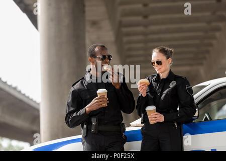 Les jeunes officiers de police avec du café et des beignes debout à côté de voiture sous le pont Banque D'Images