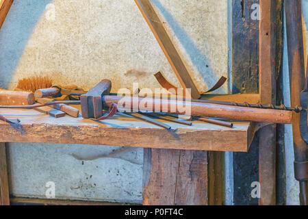 Vue dans un ancien atelier avec différents outils sur une planche en bois Banque D'Images