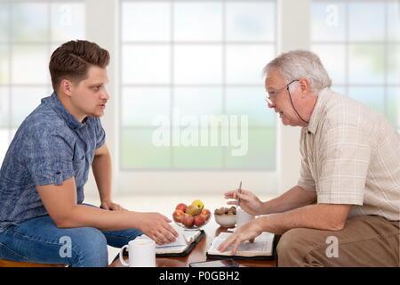Serviteur de l'église faisant du conseil à un jeune homme d'étudier la Bible Banque D'Images