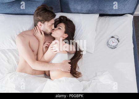 Vue du dessus de l'attractive young couple kissing in bed au matin Banque D'Images