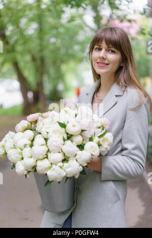 Beau bouquet de pivoines blanches dans woomans les mains . Composition florale, lumière du jour. Fond d'écran. Photo verticale Banque D'Images