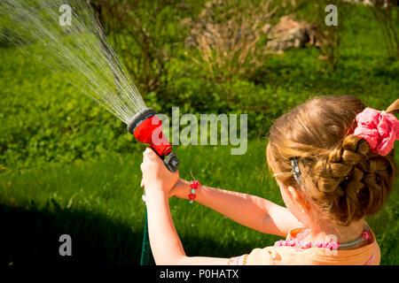 Petit enfant, adorable bébé fille, arroser les plantes, pelouse verte, de pulvérisation de flexible dans le jardin à l'arrière-cour de la maison sur un jour d'été ensoleillé Banque D'Images