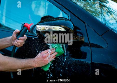 La main de l'homme le polissage de voiture noire par une autre main éponge et main courante le tuyau pour laver l'extérieur. Concept de nettoyage. Banque D'Images