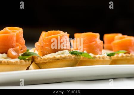 Le saumon fumé salé dans le panier se fait sous la forme d'une rose . sur une plaque blanche Banque D'Images