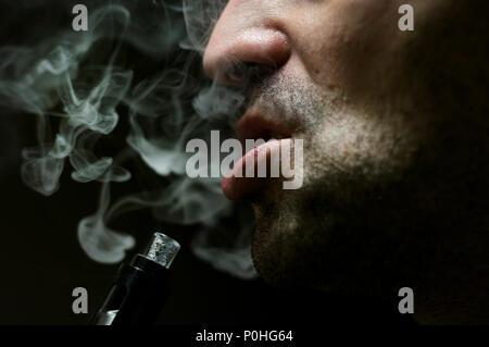 Gros plan d'un homme sur l'expiration e-cigarette sur fond noir avec lumière dramatique.