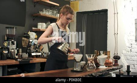 Les jeunes filles dans le quartier branché de barista coffee shop café moderne verse de l'eau bouillante sur des grains de café faire un café filtre verser sur Banque D'Images