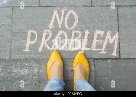 Pieds femelles avec texte pas de problème écrit sur le trottoir gris. Banque D'Images