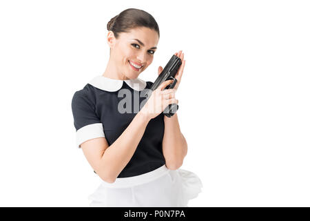 Smiling maid en uniforme holding gun isolated on white Banque D'Images