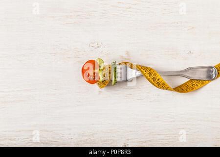 Salade fraîche sur une fourchette, ruban à mesurer, vue d'en haut. Le concept de l'alimentation, l'alimentation saine Banque D'Images
