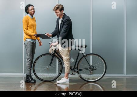 Jeune homme d'affaires signature contrat en mains de young african american collègue pendant qu'il assis sur le vélo Banque D'Images